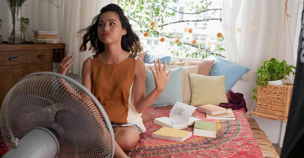 en kvinna sitter på sängen framför en fläkt